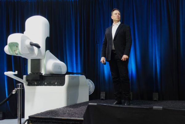 Elon Musk poses on stage with Neuralink's surgical robot